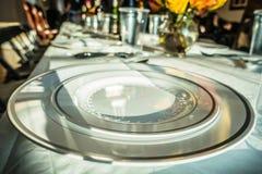 Los platos del tiempo de la familia fijaron para la cena en la tabla Fotografía de archivo