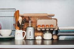 Los platos, el vajilla y los productos se colocan en una tabla de cocina foto de archivo
