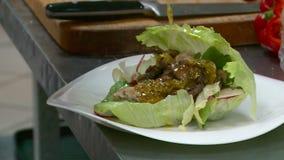 Los platos son desempeñados servicios en el restaurante por el cocinero almacen de metraje de vídeo