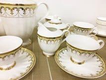 Los platos y las tazas blancos de porcelana permanecen en la tabla imagen de archivo libre de regalías