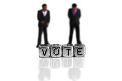 Los políticos miniatura del modelo de escala que se colocan detrás de la palabra votan Foto de archivo