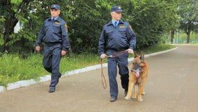 Los policías en uniforme con el perro pastor caminan a lo largo de parque almacen de video