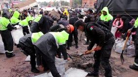 Los policías llenan las bolsas de arena para proteger las calles debidas la inundación