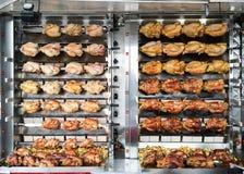 Los pollos del Rotisserie escupen asado en un mercado callejero francés Fotografía de archivo libre de regalías