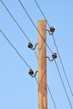 Los polos con los soportes y los alambres para la transmisión de la electricidad Fotografía de archivo