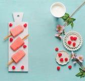Los polos rosados de las frambuesas el helado con las bayas frescas en la tabla azul, visión superior Comida del verano fotografía de archivo libre de regalías