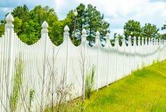 Los posts blancos de la lámpara de la cerca con los árboles se nublan el cielo Foto de archivo