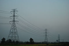 Los posts de la electricidad entre pueblo Imágenes de archivo libres de regalías