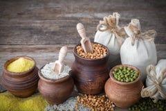 Los potes de arcilla rústicos llenaron de los granos y de los bolsos de la arpillera Imagen de archivo libre de regalías