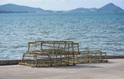 Los potes de la langosta y de cangrejo apilaron la red de pesca que cogía en la bahía foto de archivo
