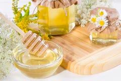 Los potes de la miel y la miel líquidos frescos llenos se pegan con las flores salvajes del verano Imágenes de archivo libres de regalías