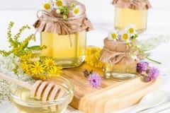 Los potes de la miel y la miel líquidos frescos llenos se pegan con las flores salvajes del verano Fotografía de archivo