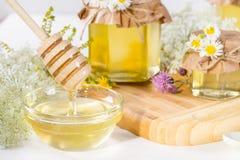 Los potes de la miel y la miel líquidos frescos llenos se pegan con las flores salvajes del verano Foto de archivo libre de regalías