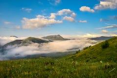Los prados hermosos en montañas son cubiertos por las nubes Fotografía de archivo