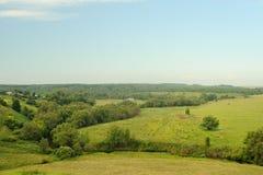 Los prados verdes acercan al pequeño río con el cielo azul y el bosque Imagenes de archivo