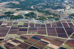 Los prados y los campos del arroz acercan al pequeño pueblo Imágenes de archivo libres de regalías
