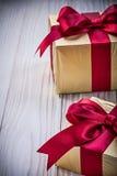 Los presentes de cumpleaños con rojo arquean en concepto de los días de fiesta del tablero de madera foto de archivo