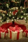 Los presentes debajo de la cinta roja adornada brillante del árbol de navidad envolvieron los regalos imagenes de archivo