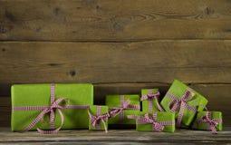 Los presentes verdes con rojo y blanco comprobaron la cinta en de madera Fotos de archivo libres de regalías