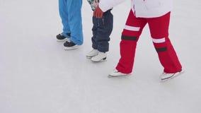Los primeros pasos de un niño joven en patines La mamá y el papá enseñan a un niño a patinar y a llevar a cabo sus manos en el hi metrajes