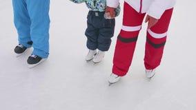 Los primeros pasos de un niño joven en patines La mamá y el papá enseñan a un niño a patinar y a llevar a cabo sus manos en el hi almacen de metraje de vídeo