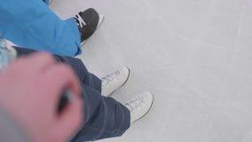 Los primeros pasos de un niño joven en patines La mamá y el papá enseñan a su niño a patinar y a llevar a cabo su mano Familia y  almacen de video