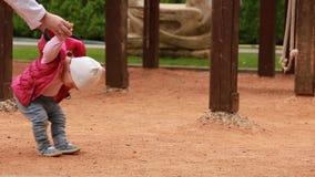 Los primeros pasos del pequeño bebé lindo en el patio en la ciudad parquean almacen de video