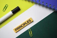 Los principios mandan un SMS en notas pegajosas con concepto del escritorio de oficina fotografía de archivo