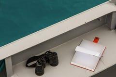 Los prismáticos y una libreta para los cuadernos se fueron en la cubierta de un buque de guerra Fotos de archivo libres de regalías