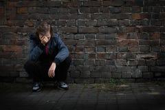 Los problemas de adolescentes, niño triste que se sienta en un cuarto oscuro piensan Foto de archivo