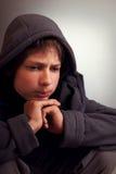 Los problemas de adolescentes, niño triste que se sienta en un cuarto oscuro piensan Imágenes de archivo libres de regalías