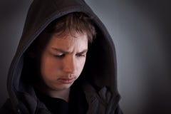Los problemas de adolescentes, niño triste que se sienta en un cuarto oscuro piensan Foto de archivo libre de regalías