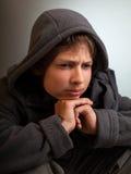 Los problemas de adolescentes, niño triste que se sienta en un cuarto oscuro piensan Imagen de archivo libre de regalías