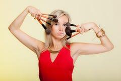 Los procedimientos de la belleza, mujer sostienen cepillos del maquillaje cerca de cara. Fotografía de archivo libre de regalías