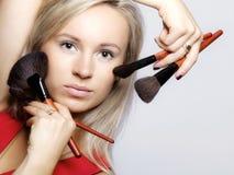 Los procedimientos de la belleza, mujer sostienen cepillos del maquillaje cerca de cara Foto de archivo