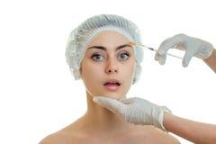 Los procedimientos de las conductas del Cosmetologist en guantes con el llenador en la cara de una chica joven tienen primer foto de archivo libre de regalías