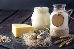 Los productos agrícolas de Eco ordeñan, queso, crema agria, yogur, huevos en fondo de madera oscuro El concepto de hogar hizo la  Foto de archivo libre de regalías