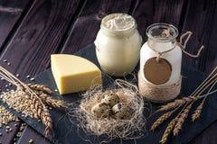 Los productos agrícolas de Eco ordeñan, queso, crema agria, yogur, huevos en fondo de madera oscuro El concepto de hogar hizo la  Fotografía de archivo