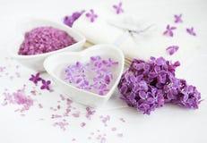 Los productos de la toalla y del masaje del balneario con la lila florecen foto de archivo libre de regalías