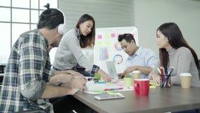 Los profesionales creativos recolectaron en la mesa de reuniones para discuten las aplicaciones importantes el nuevo proyecto de  almacen de metraje de vídeo