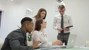 Los profesionales jovenes trabajan en compañía, usando el ordenador portátil y la tableta almacen de metraje de vídeo