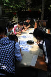 Los profesores son enseñando niños a cómo escribir el callig Foto de archivo libre de regalías