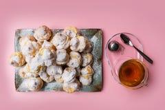 Los profiteroles hechos en casa sirvieron en una placa con una taza de té en un fondo rosado Endecha plana fotografía de archivo libre de regalías