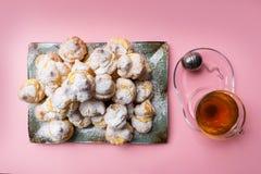 Los profiteroles hechos en casa sirvieron en una placa con una taza de té en un fondo rosado Endecha plana foto de archivo