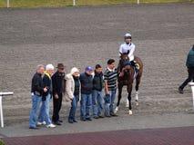 Los propietarios del jinete y del caballo presentan con el caballo después de raza Fotos de archivo libres de regalías