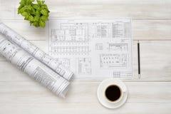 Los proyectos, la taza de café y el houseplant están en superficie de madera Fotos de archivo