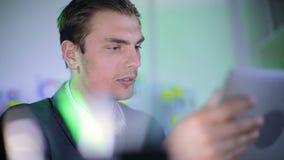 Los pulgares del hombre joven atento con noticias en la tableta metrajes