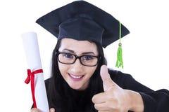 Los pulgares suben a la mujer de la graduación Imágenes de archivo libres de regalías