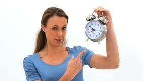 Los puntos de la mujer en un reloj entonces abren su boca en sorpresa almacen de metraje de vídeo