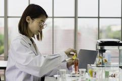 Los qu?micos trabajan el laboratorio por la ma?ana, con las muestras trabajando con las sustancias qu?micas l?quidas coloridas, l fotografía de archivo libre de regalías